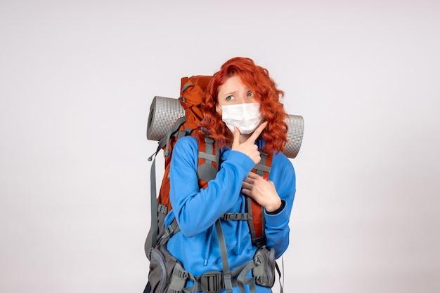 Вид спереди туристка в маске с ее рюкзаком мышления
