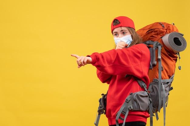 Turista femminile di vista frontale con lo zaino e la maschera che indica con il dito qualcosa