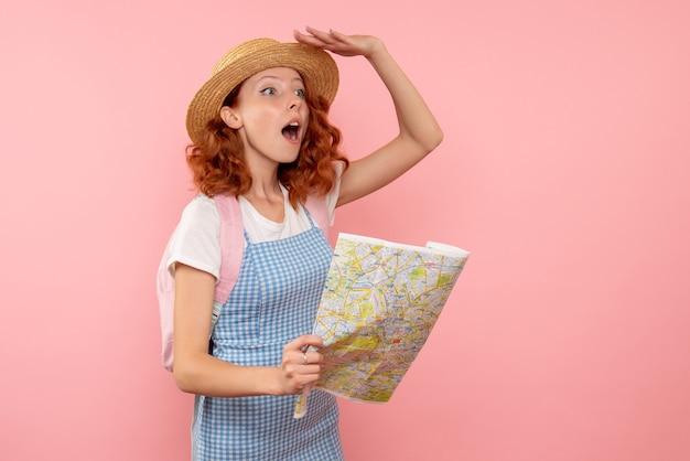 Turista femminile di vista frontale con la mappa che prova a trovare la direzione nel paese straniero