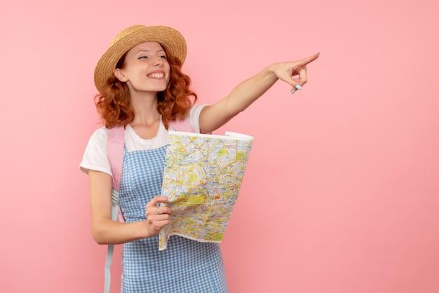 Вид спереди туристка с картой пытается найти направление в чужом городе