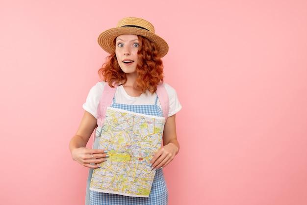 外国の都市で方向を見つけようとしている地図と正面図の女性観光客
