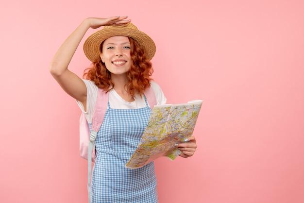Вид спереди туристка с картой пытается найти направление в чужой стране