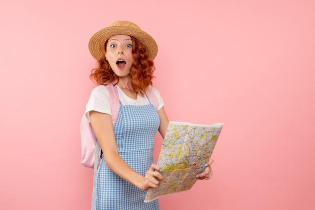 外国で方向を見つけようとしている地図と正面図の女性観光客