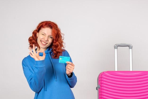 ピンクのバッグと銀行カードで正面図の女性観光客
