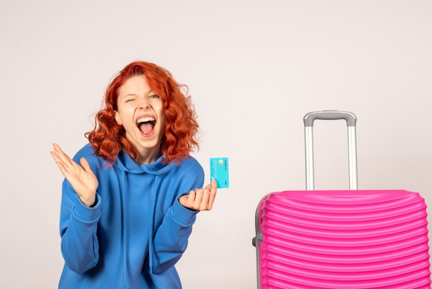 ピンクのバッグと銀行カードを保持している正面図の女性観光客