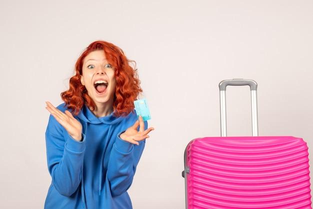 Женщина-туристка с розовой сумкой и банковской картой, вид спереди