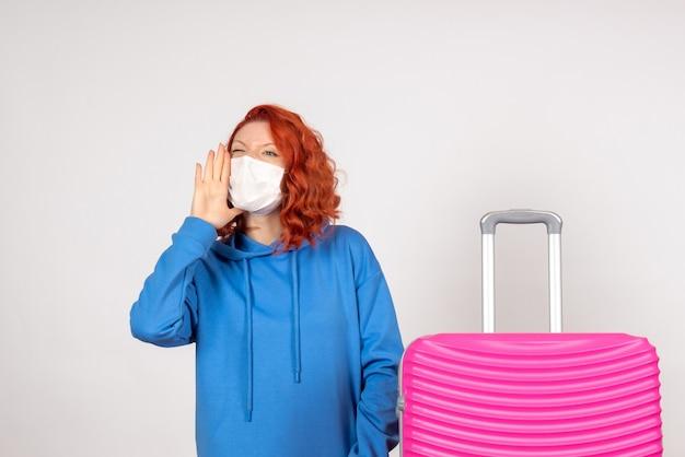 Вид спереди туристка с розовой сумкой, звонящей