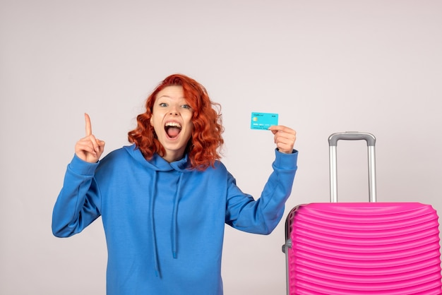 Front view female tourist with pink bag and holding bank card
