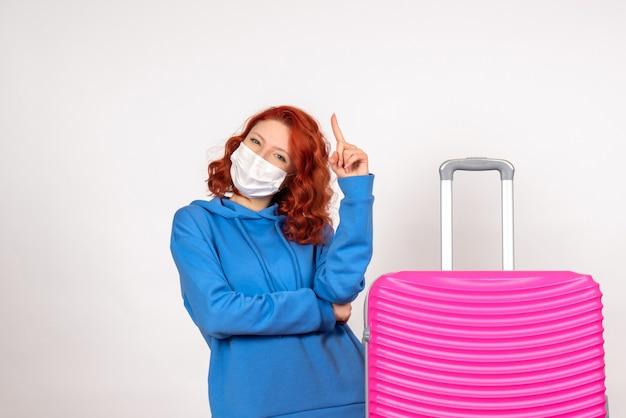 Вид спереди туристка с розовой сумкой в маске