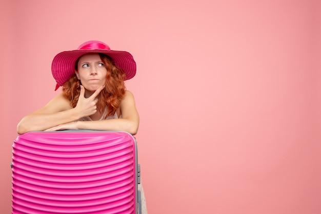 Vista frontale del turista femminile con borsa rosa sulla parete rosa