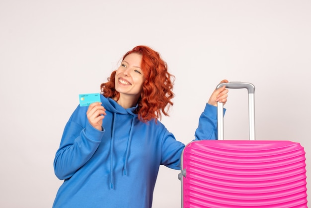 Vista frontale del turista femminile con borsa rosa sul muro bianco