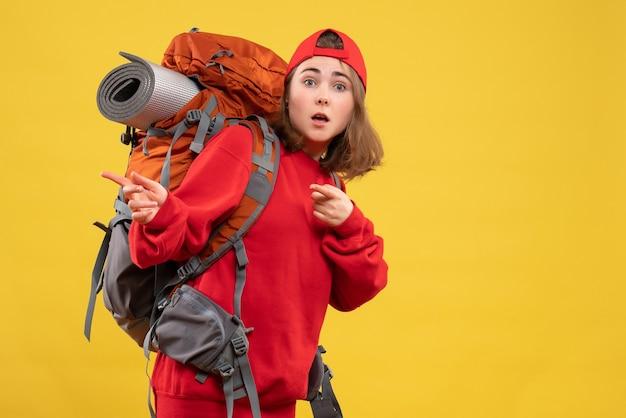 Путешественница, вид спереди с рюкзаком, указывающим налево