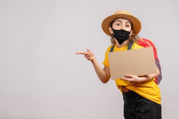 Vista frontale della donna che viaggia con zaino tenendo il cartone rivolto a sinistra sul muro grigio