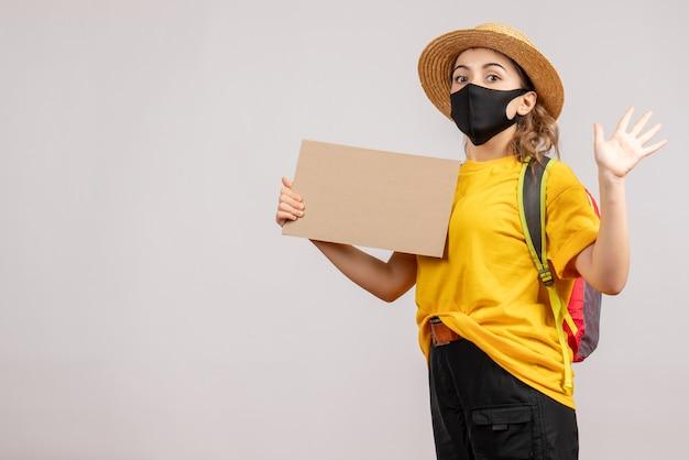 Vista frontale della donna che viaggia con lo zaino che tiene cartone agitando la mano sul muro grigio