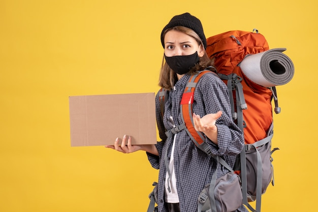 Front view of female traveller with black mask and backpack holding up cardboard
