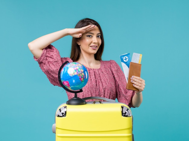 Front view female in trip holding wallet with tickets on a blue background woman voyage vacation sea trip journey