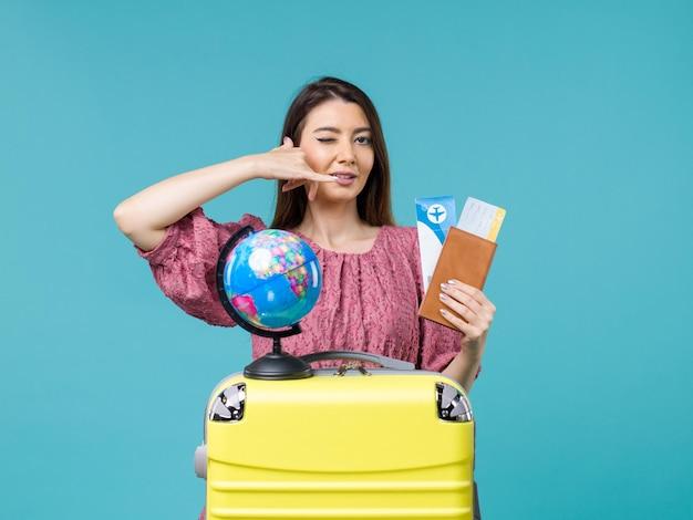 Donna di vista frontale nel portafoglio della tenuta di viaggio con i biglietti su fondo azzurro viaggio della donna di viaggio di vacanza di viaggio del mare di viaggio