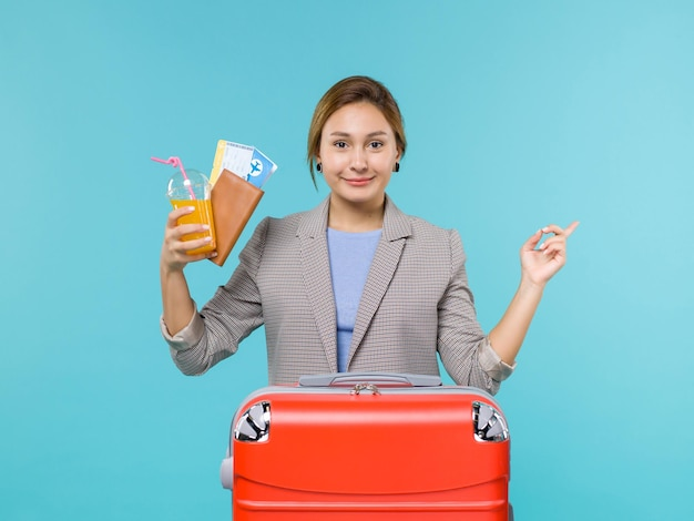 Femmina di vista frontale in bevanda e biglietti della tenuta di vacanza su fondo blu viaggio di viaggio aereo di vacanza di viaggio del mare che viaggia