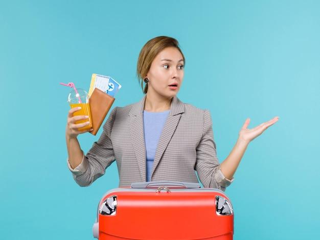 Femmina di vista frontale nella bevanda della tenuta di vacanza e biglietti sullo sfondo blu viaggio di vacanza di viaggio di mare in viaggio