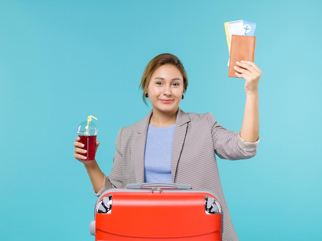 Front view female in vacation holding fresh cherry juice and tickets on a blue background voyage trip plane vacation travel