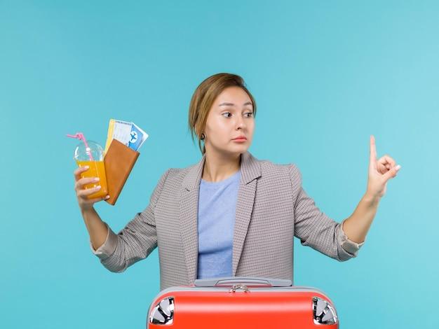 Femmina di vista frontale in vacanza che tiene bevanda fresca e biglietti su sfondo blu viaggio mare viaggio viaggio viaggio viaggio