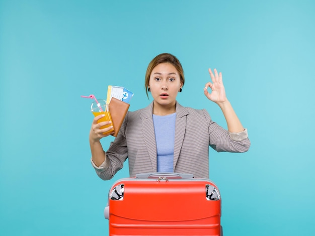 Femmina di vista frontale in vacanza che tiene bevanda fresca e biglietti sullo sfondo blu viaggio di vacanza viaggio di mare in viaggio