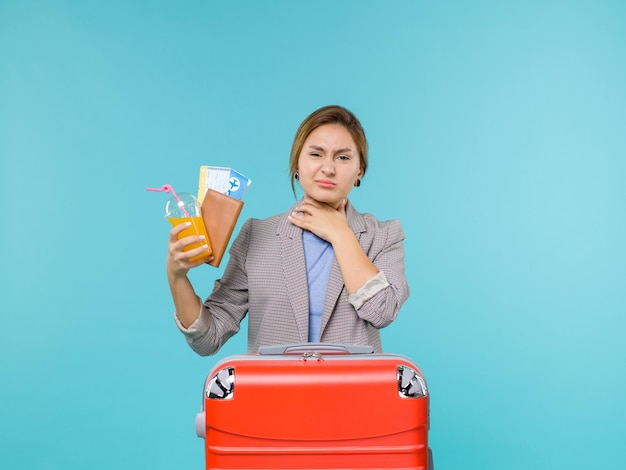 Front view female in vacation holding fresh drink and tickets on blue background sea vacation voyage travelling