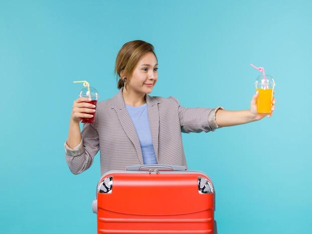 Femmina di vista frontale in vacanza che tiene le bevande fresche sul viaggio aereo di viaggio di vacanza del viaggio del mare del fondo blu che viaggiano