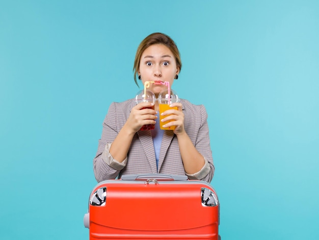 Femmina di vista frontale in vacanza che tiene le bevande fresche sull'aereo di viaggio di vacanza di viaggio di viaggio del mare del fondo blu