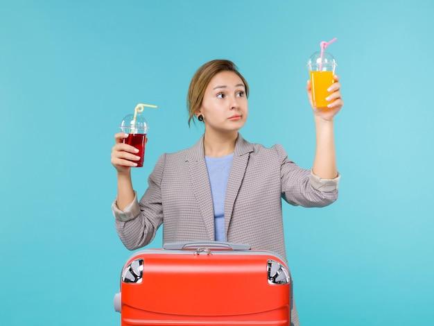 Femmina di vista frontale in vacanza che tiene le bevande fresche sull'aereo di mare di viaggio di viaggio di viaggio di viaggio di sfondo blu