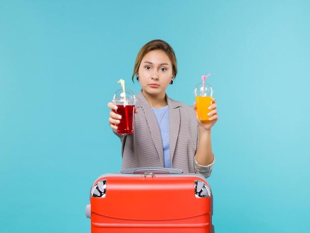 Femmina di vista frontale in vacanza che tiene le bevande fresche sull'aereo di mare di viaggio di viaggio di viaggio di viaggio del pavimento blu