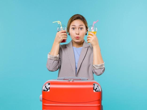 Femmina di vista frontale in vacanza che tiene le bevande fresche sull'aereo di mare di viaggio di viaggio di viaggio di viaggio di sfondo azzurro