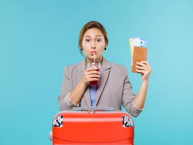 Femmina di vista frontale in vacanza che tiene un bicchiere fresco di succo di frutta e biglietti sullo sfondo blu viaggio aereo viaggio viaggio viaggio mare