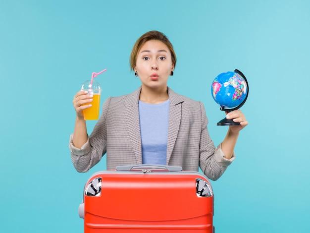 Femmina di vista frontale in vacanza che tiene il succo fresco e il globo sul viaggio di viaggio di viaggio di vacanza del mare del fondo blu