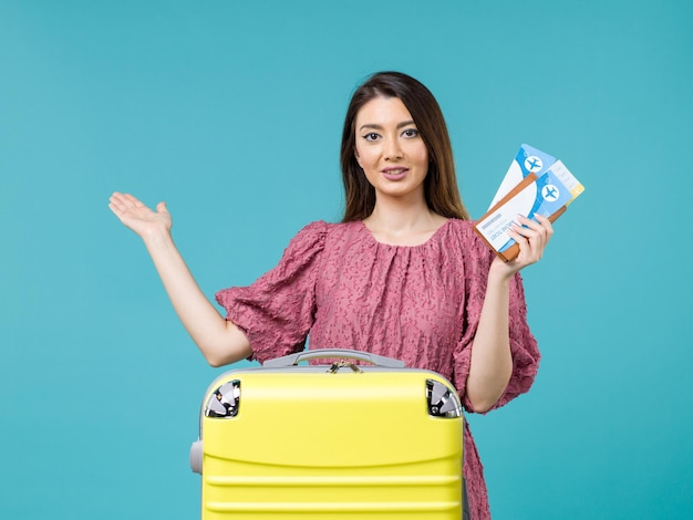 Donna di vista frontale in vacanza che tiene i suoi biglietti su sfondo blu viaggio viaggio donna estate vacanza mare