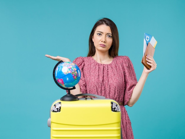 Front view female in vacation holding her wallet and ticket on a light blue background sea trip vacation woman journey voyage