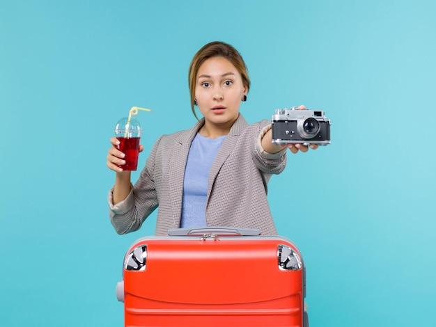 Femmina di vista frontale in vacanza che tiene il succo con la macchina fotografica su fondo azzurro viaggio viaggio vacanza viaggio idrovolante