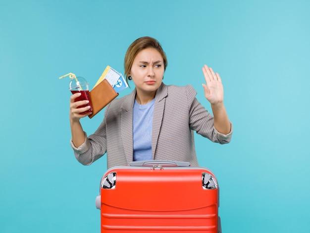 Vista frontale femminile in vacanza tenendo il succo con i biglietti su sfondo azzurro viaggio vacanza viaggio viaggio idrovolante