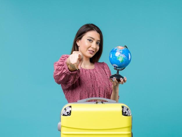 Femmina di vista frontale in vacanza che tiene piccolo globo della terra sull'estate di vacanza di viaggio della donna del mare di viaggio del fondo blu