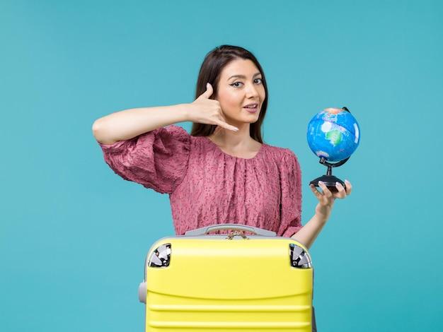 Femmina di vista frontale in vacanza che tiene piccolo globo della terra sull'estate di vacanza di viaggio della donna di viaggio del mare del fondo blu
