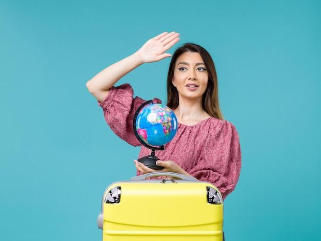 Femmina di vista frontale in vacanza che tiene piccolo globo della terra sull'estate di viaggio di viaggio della donna di vacanza del mare del fondo blu