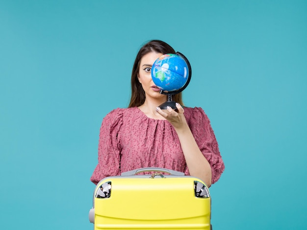 Front view female in vacation holding little earth globe on light blue background sea vacation journey summer woman trip