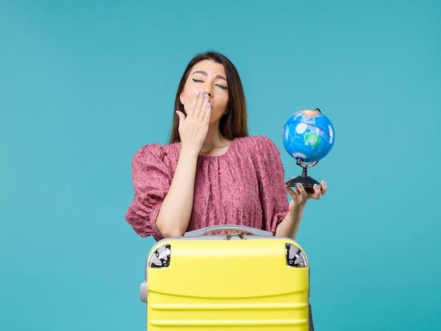 Femmina di vista frontale in vacanza che tiene piccolo globo della terra e che sbadiglia sull'estate di vacanza di viaggio della donna del mare di viaggio del fondo blu