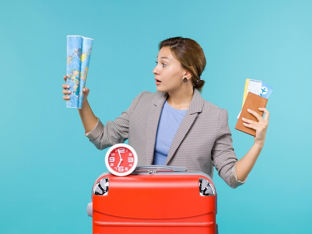 Front view female in vacation holding map and tickets on a blue background plane travel voyage journey trip vacation sea