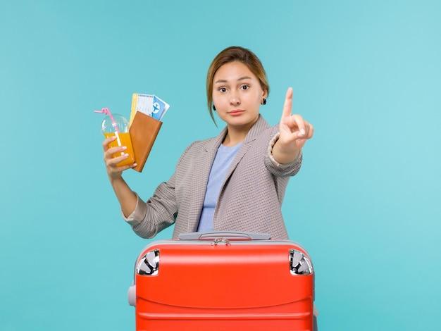 Femmina di vista frontale in vacanza che tiene i biglietti sul viaggio per mare viaggio aereo blu scrivania
