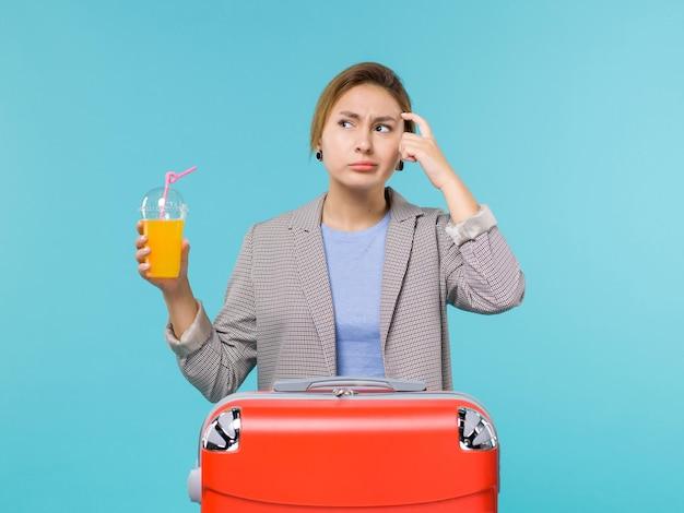 Femmina di vista frontale in vacanza con la grande borsa rossa che tiene il succo fresco sul viaggio di viaggio di viaggio aereo di vacanza del mare del fondo blu