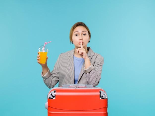 Femmina di vista frontale in vacanza con la sua borsa rossa che tiene il succo fresco sul viaggio di viaggio di viaggio aereo di vacanza di mare del fondo blu