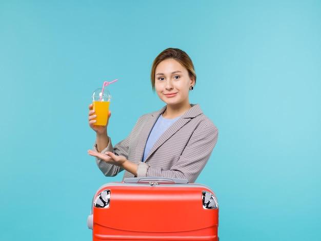 Femmina di vista frontale in vacanza con la sua borsa rossa che tiene il succo fresco sul viaggio di viaggio di viaggio del mare di viaggio aereo di vacanza del fondo blu