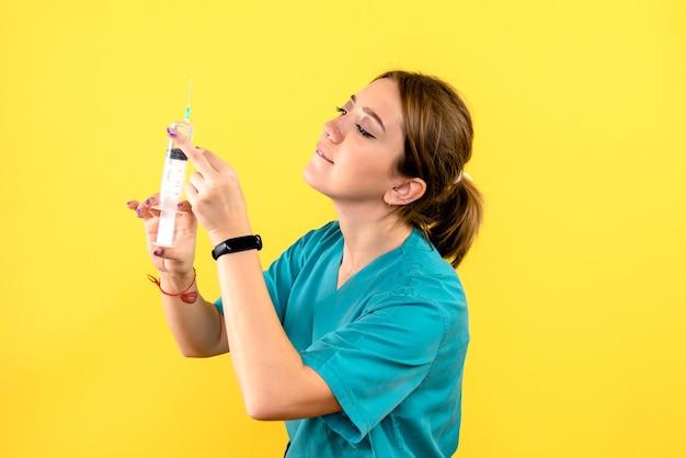 Vista frontale dell'iniezione femminile della tenuta del veterinario sulla parete gialla