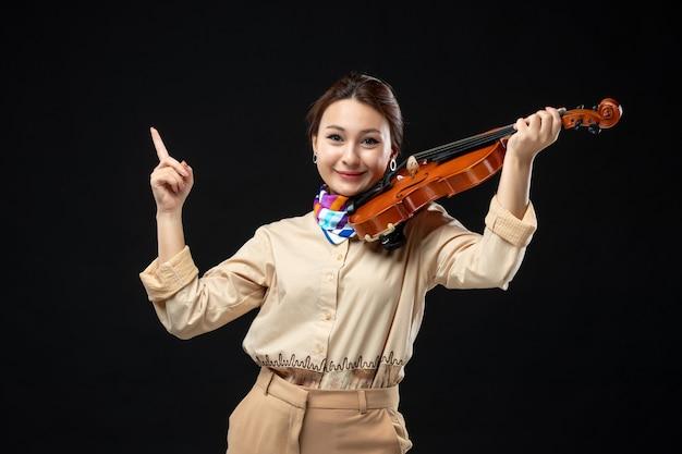 Vista frontale violinista femminile che tiene il suo violino su un muro scuro donna concerto melodia emozione suonare strumento musica
